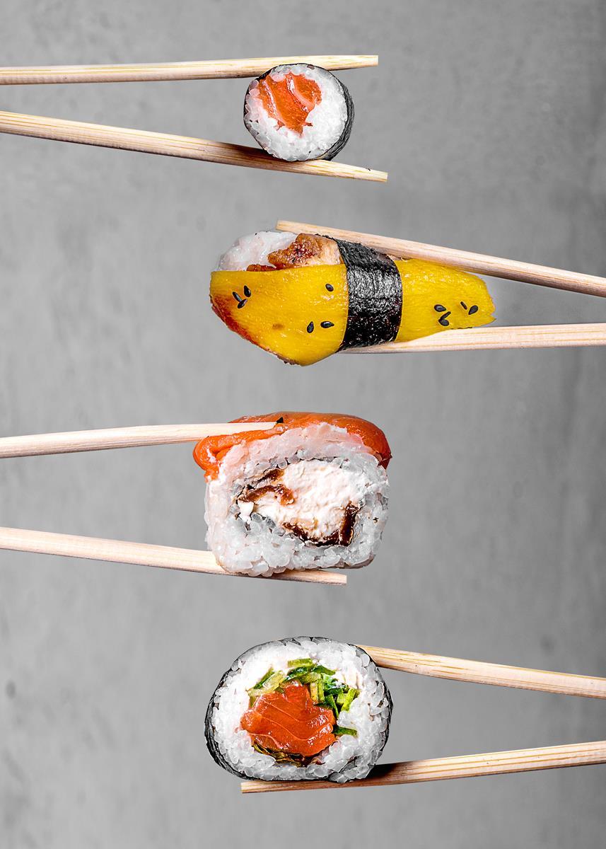 4 rodzaje sushi trzymane pałeczkami